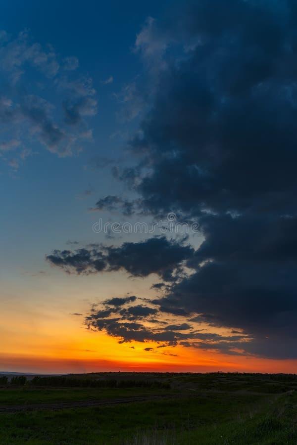De hemel met heldere wolken die door de zon na zonsondergang over het gebied worden aangestoken stock fotografie