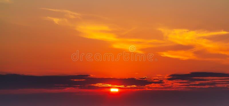 De hemel tijdens een kleurrijke, heldere oranje zonsondergang, de stralen van de zon maakt hun manier door de wolken stock afbeelding