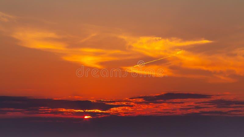 De hemel tijdens een kleurrijke, heldere oranje zonsondergang, de stralen van de zon maakt hun manier door de wolken royalty-vrije stock foto