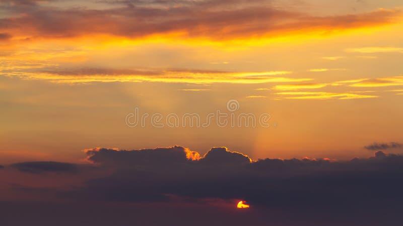 De hemel tijdens een kleurrijke, heldere oranje zonsondergang, de stralen van de zon maakt hun manier door de wolken royalty-vrije stock foto's