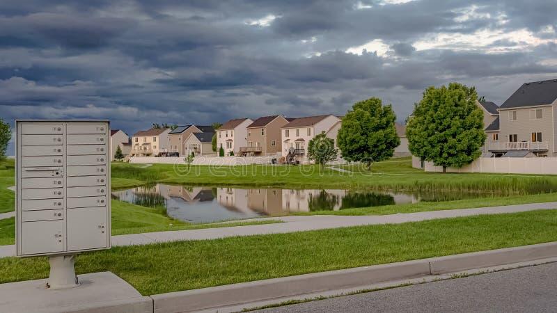 De Hemel van het panoramakader met grijze wolken over huizen en vijver amid een enorm grasrijk terrein wordt gevuld dat royalty-vrije stock afbeeldingen