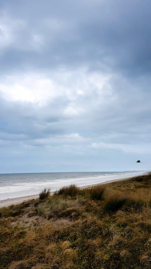 De hemel van het de zomeronweer over het strand met regen stock afbeeldingen