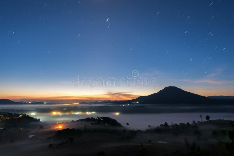 De hemel van de landschapsnacht met sterstaart en mist in ochtend sunriseat stock afbeeldingen