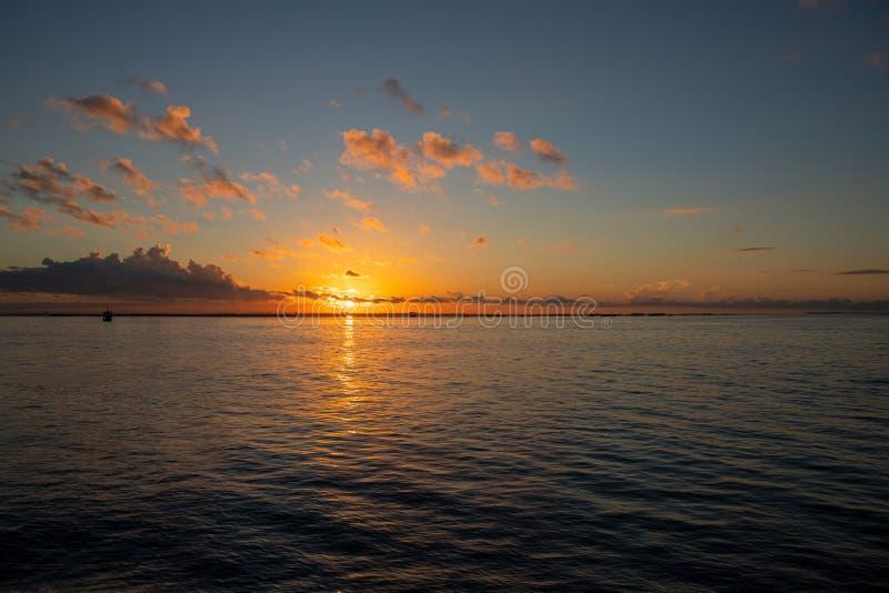 De hemel van de ochtenddauw met oranje wolk en zon De foto van de kustzonsopgang Trillende oranje hemel met zon over overzees royalty-vrije stock fotografie