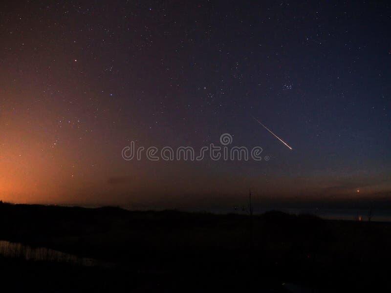 De hemelsterren Orion van de meteoornacht en het Venus van de Stierconstellatie over overzees royalty-vrije stock fotografie