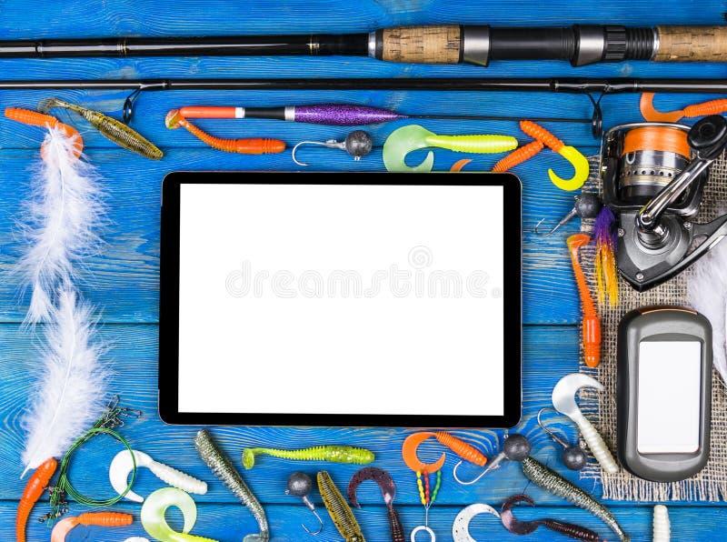 De hengel, de uitrustingen en het vissende aas, spoel op houten raadsachtergrond met tabletcomputer isoleerden het witte scherm,  stock foto's