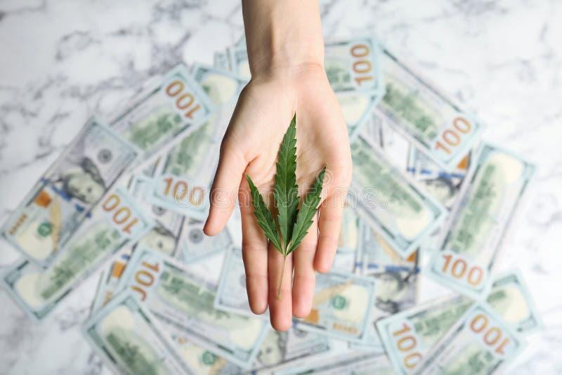 De hennepblad van de vrouwenholding over geld op lijst stock foto's
