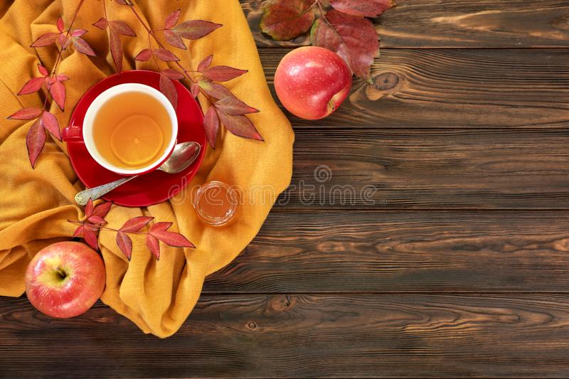 De herfst achtergrondconcept - rode kop thee met stuk van citroen, rode vers gevallen bladeren, rode appelen, honing op een houte stock afbeeldingen