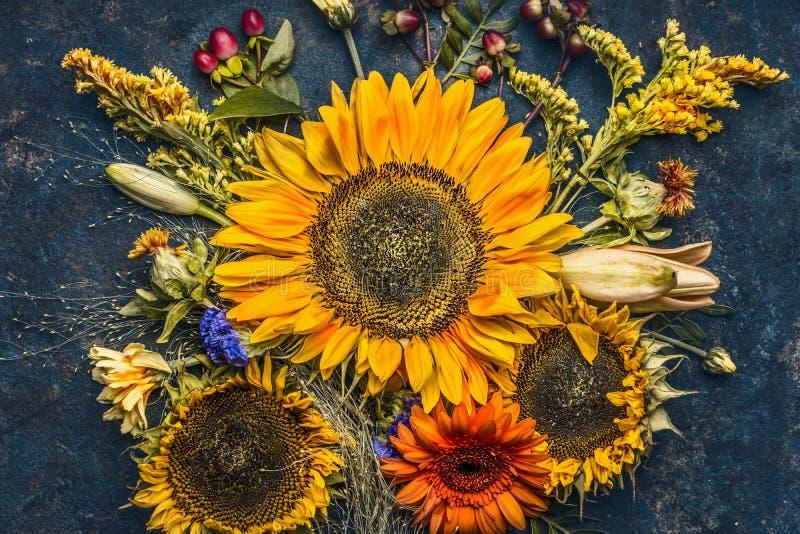 De herfst bloeit en verlaat samenstelling met zonnebloemen op donkere rustieke achtergrond, hoogste mening stock afbeelding