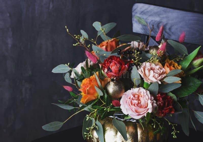 De herfst bloemenboeket in punpkinvaas op zwarte stoel royalty-vrije stock afbeeldingen