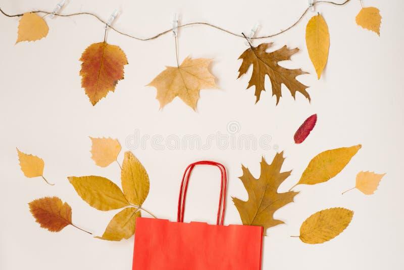 De herfst die met kortingen winkelen Een rode document het winkelen zak met de herfst gele bladeren die uit het gluren De ruimte  stock fotografie