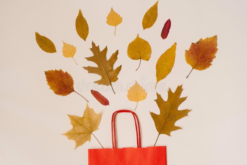 De herfst die met kortingen winkelen De herfstverkoop Een rode document het winkelen zak met de herfst gele bladeren die uit glur royalty-vrije stock afbeeldingen