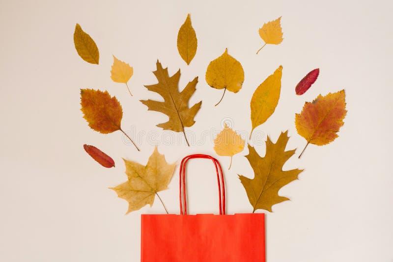De herfst die met kortingen winkelen De herfstverkoop Een rode document het winkelen zak met de herfst gele bladeren die uit het  stock afbeeldingen