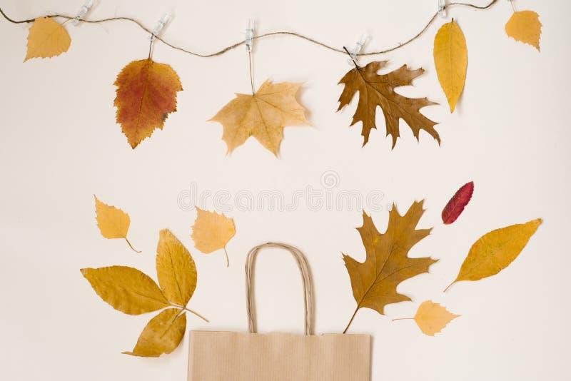 De herfst die met kortingen winkelen De herfstverkoop Het document van kraftpapier beige het winkelen zak, waarvan de gele blader stock foto's