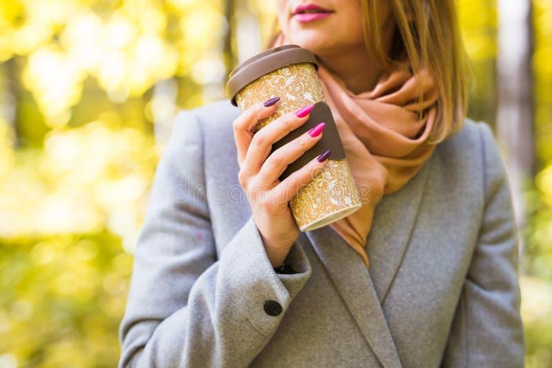 De herfst, drank en koffieconcept - sluit omhoog van vrouw in grijze laag met kop van koffie royalty-vrije stock foto