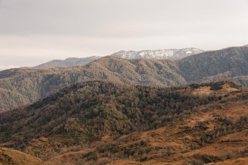 De herfst Georgisch landschap van hooggebergte en heuvels met oranje bomen royalty-vrije stock afbeelding