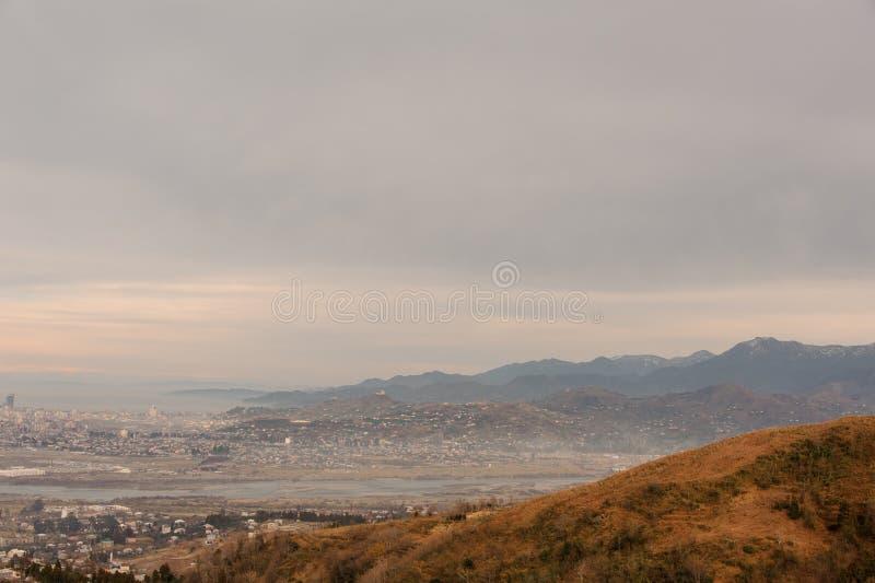 De herfst Georgisch landschap van weinig Batumi-stad op de achtergrond van bergen in oranje kleuren royalty-vrije stock foto