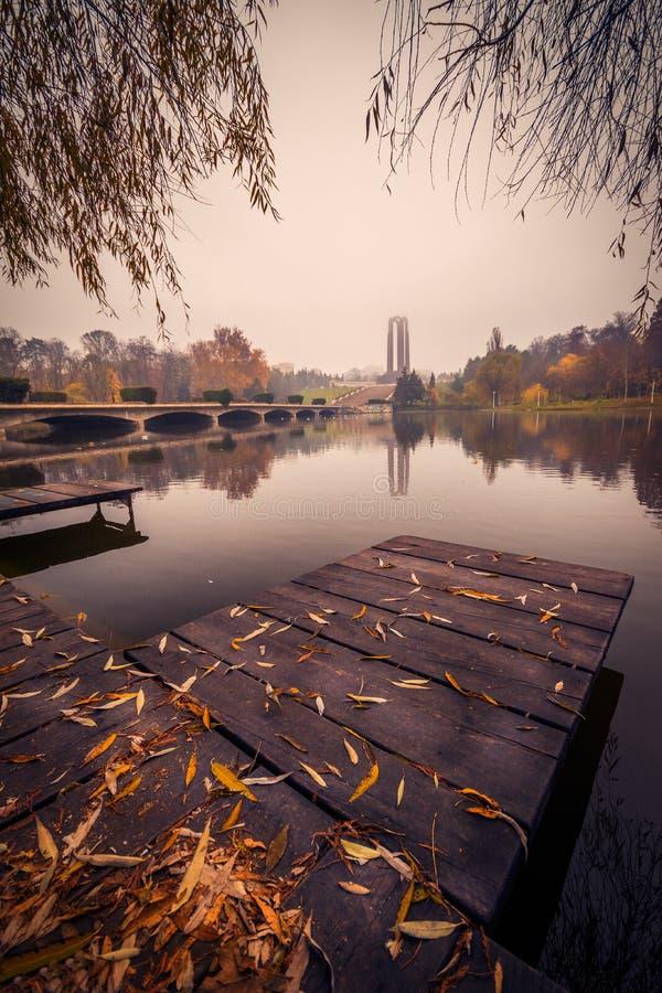 De herfst in het park dichtbij het meer met bladeren ter plaatse royalty-vrije stock afbeeldingen