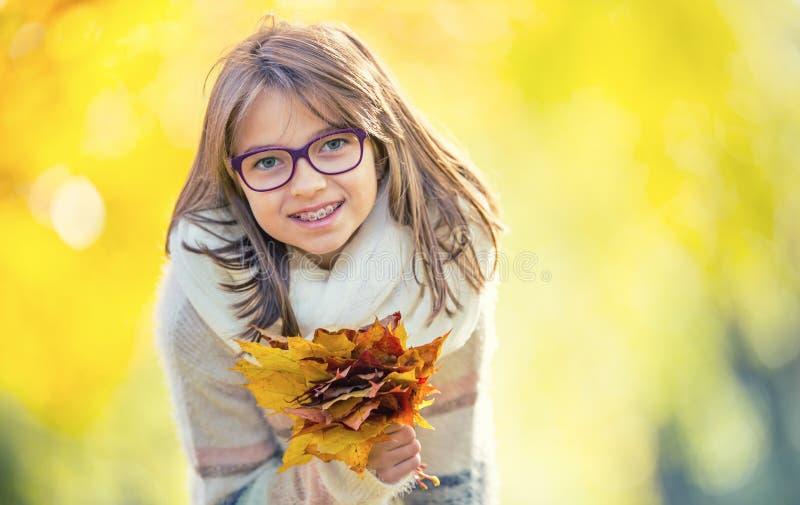 De herfst Portret van een glimlachend jong meisje dat in haar hand houdt een boeket van de herfstesdoorn verlaat royalty-vrije stock foto
