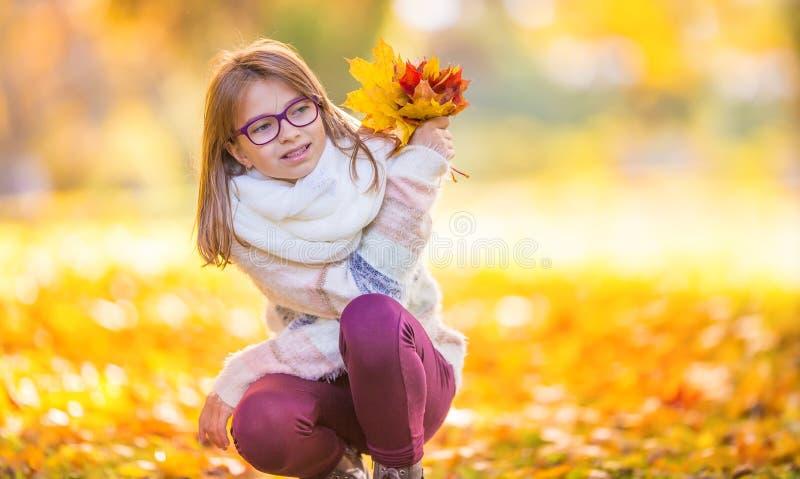 De herfst Portret van een glimlachend jong meisje dat in haar hand houdt een boeket van de herfstesdoorn verlaat stock fotografie