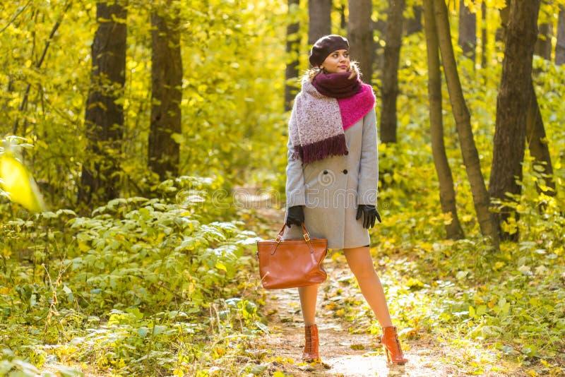 De herfst, seizoen en mensenconcept - vrouw in laag met bruine zak die zich in de herfstpark bevinden royalty-vrije stock afbeeldingen