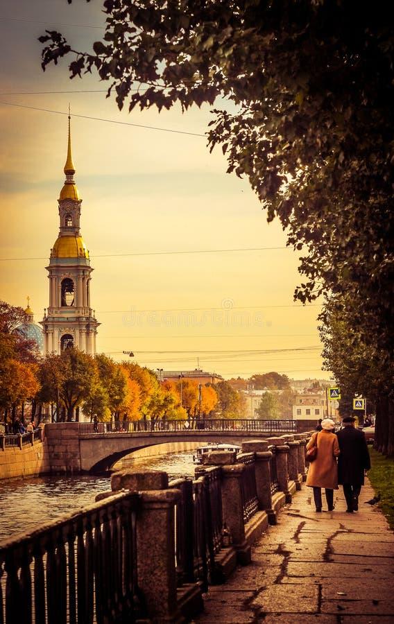 de herfst in de stad, bejaarde mensen die rond de stad, mensen lopen loopt langs het kanaal op de straat, Kerk in de stad op royalty-vrije stock fotografie