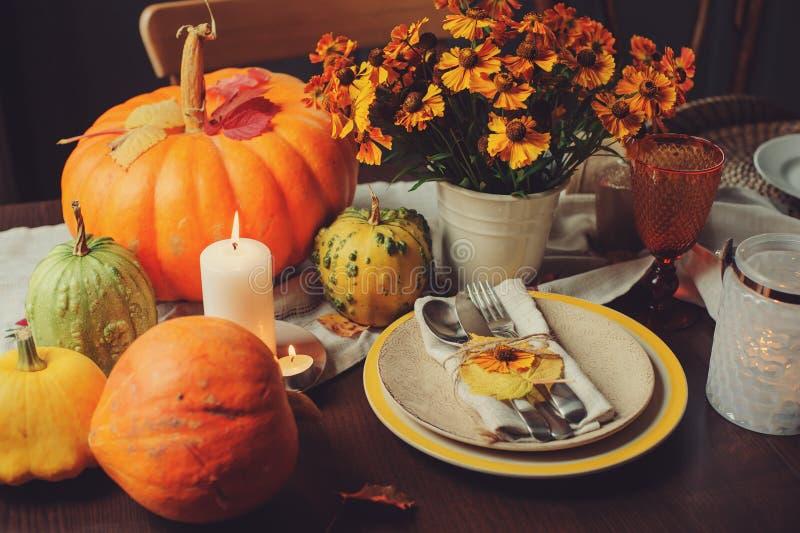 De herfst traditionele seizoengebonden lijst die thuis met pompoenen, kaarsen en bloemen plaatsen stock afbeeldingen