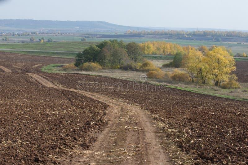 De herfst, is de weg ongeplaveid, vers geploegd gebied, een heuvel covere royalty-vrije stock foto