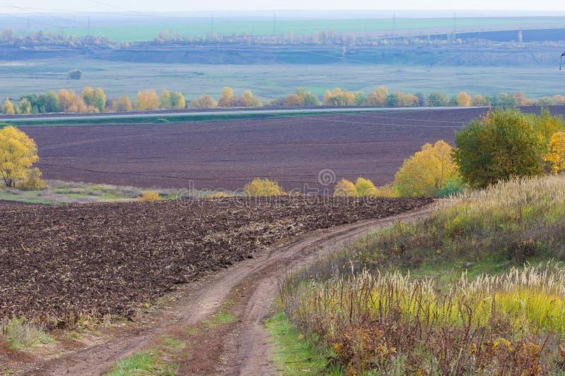 De herfst, is de weg ongeplaveid, vers geploegd gebied, een heuvel covere royalty-vrije stock foto's