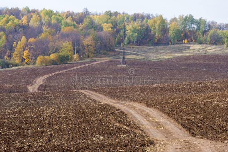 De herfst, is de weg ongeplaveid, vers geploegd gebied, een heuvel covere royalty-vrije stock fotografie