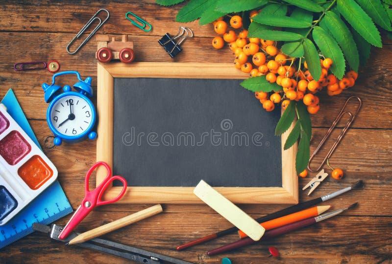 De herfstachtergrond, bord, lijsterbessentak, schooltoebehoren stock foto's