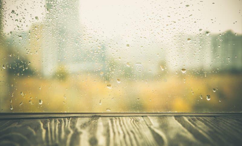 De herfstachtergrond - houten lijst voor rainiy venster stock foto