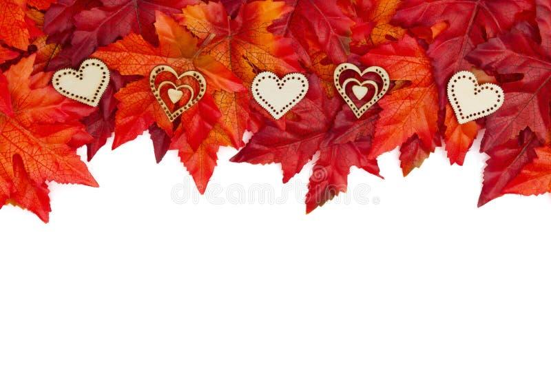 De herfstachtergrond met houten harten en rood en oranje dalingsverlof stock foto