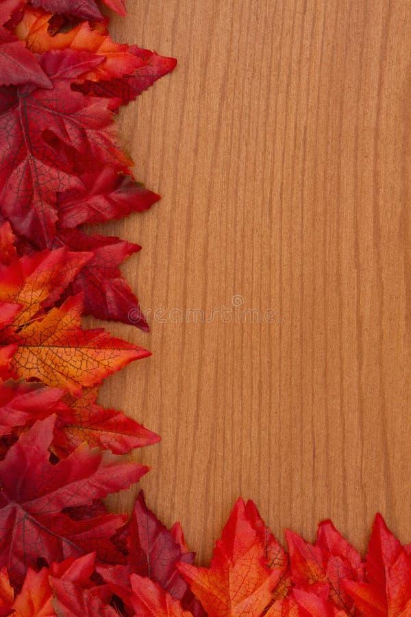 De herfstachtergrond met rode en oranje dalingsbladeren op hout royalty-vrije stock foto's