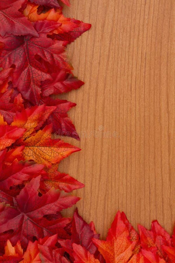 De herfstachtergrond met rode en oranje dalingsbladeren op hout royalty-vrije stock afbeeldingen
