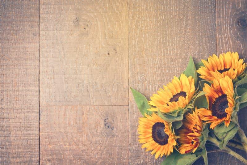 De herfstachtergrond met zonnebloemen op houten lijst Mening van hierboven Retro filtereffect royalty-vrije stock afbeeldingen