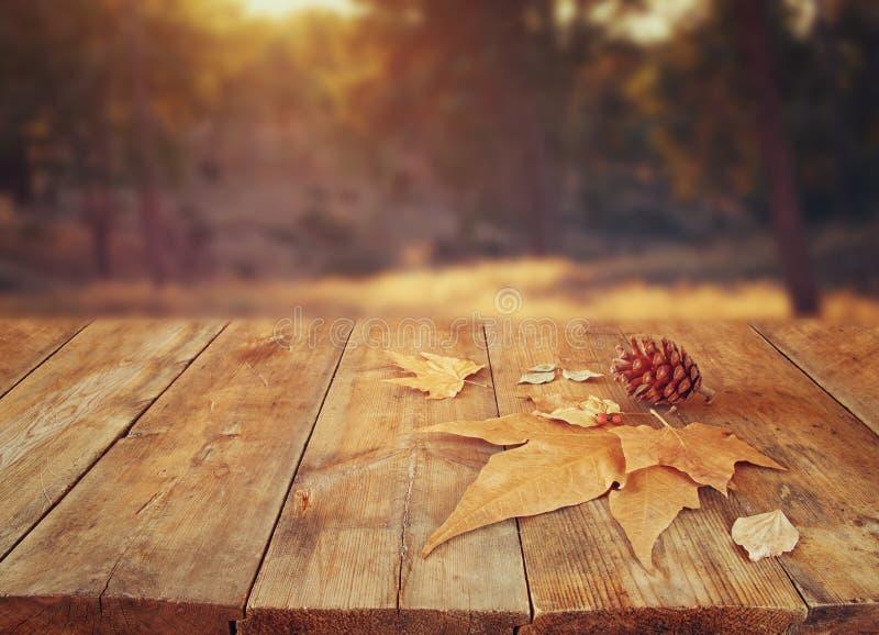 De herfstachtergrond van gevallen bladeren over houten lijst en bos backgrond met lensgloed en zonsondergang stock foto