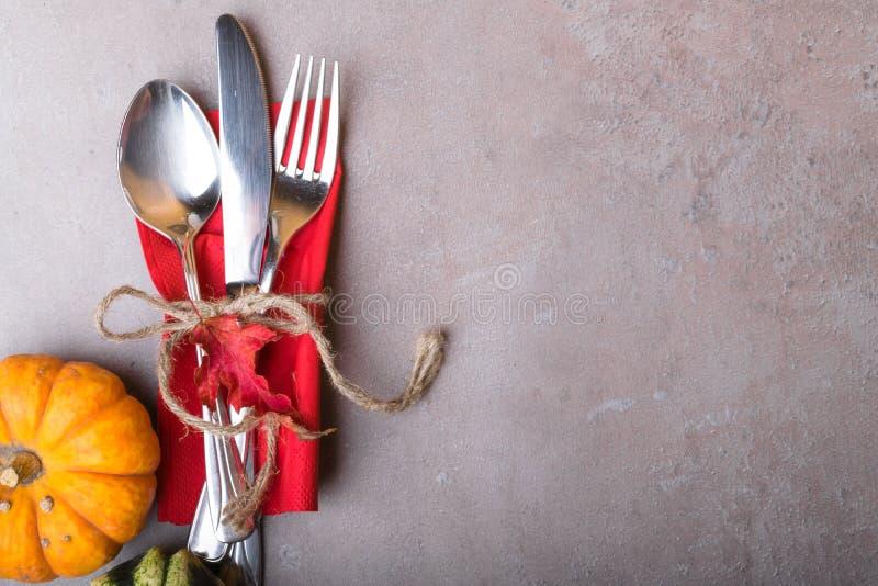 De herfstachtergrond van gevallen rood verlof en pompoen met zilveren plaats die op steenlijst plaatsen Thanksgiving dayconcept stock afbeeldingen