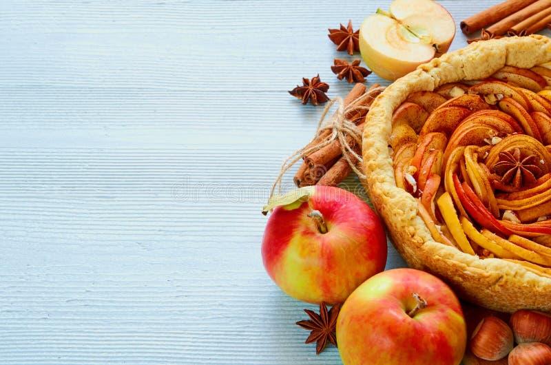 De de herfstappeltaart op de houten raad verfraaide met verse appelen, hazelnoten, kruiden - anijsplant, kaneel op de grijze keuk stock afbeelding