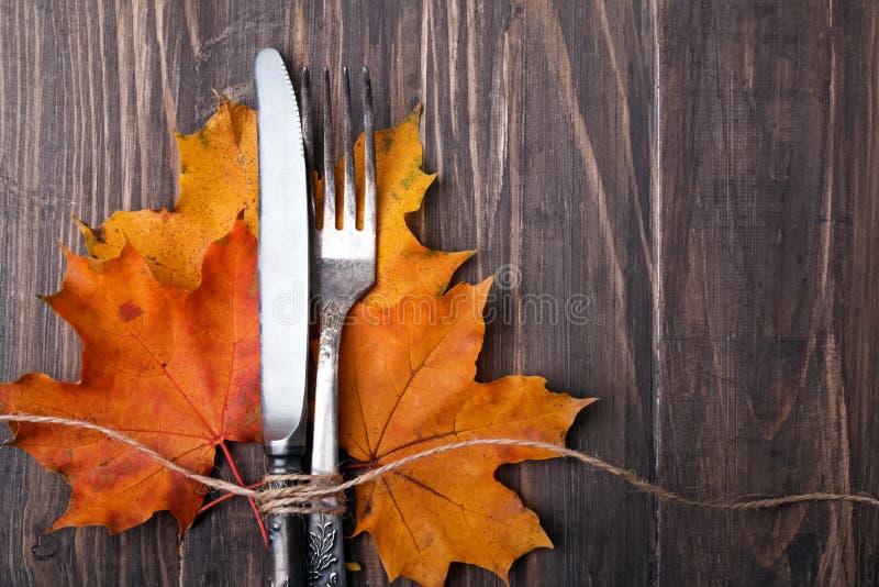 De herfstbladeren, mes en vork stock fotografie