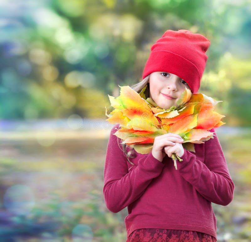 De herfstbladeren van het kindmeisje op natuurlijke achtergrond stock afbeelding