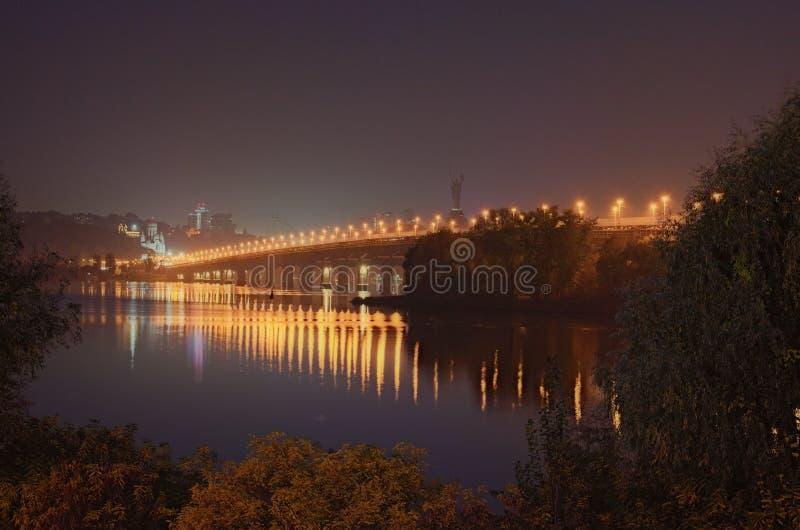 De herfstcityscape met Paton-brug over Dnieper-rivier bij nacht Het monument van het vaderland bij de achtergrond royalty-vrije stock foto