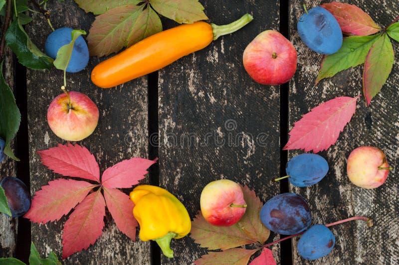 De herfstgroenten en vruchten op een oude houten achtergrond in openlucht royalty-vrije stock fotografie