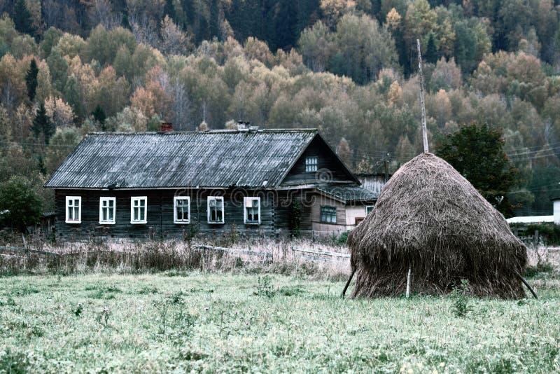 De herfstlandschap in het Noorden van Rusland met dorpshuis en hooiberg stock foto's