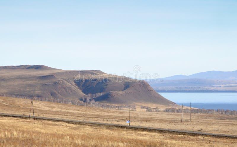 De herfstlandschap met blauw meer en met vlotte die heuvels met droog geel gras onder blauwe hemel worden behandeld stock afbeelding
