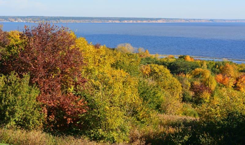 De herfstlandschap met bos op rivierbank Rode, oranje, gele en groene kleuren van bomengebladerte stock afbeeldingen