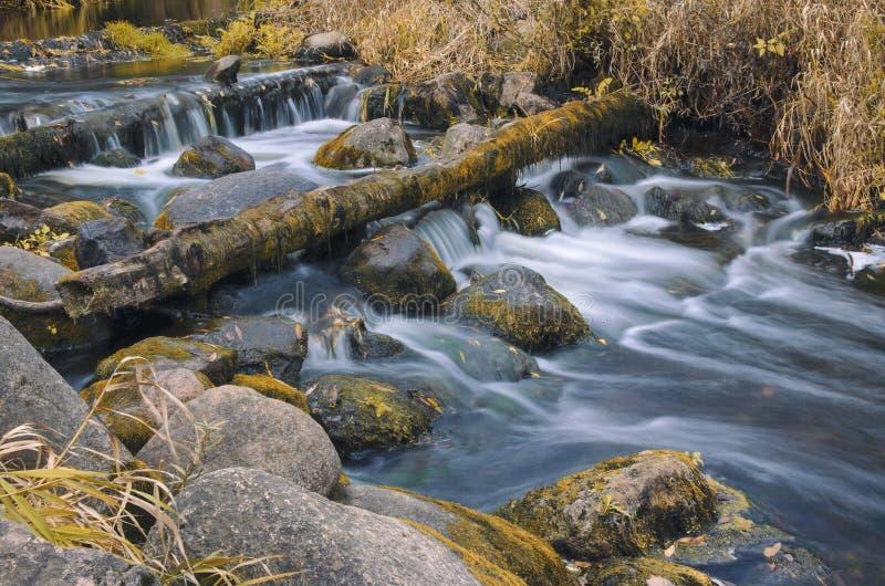 De herfstlandschap met een rivier die regelmatig tussen de keien stromen royalty-vrije stock afbeeldingen