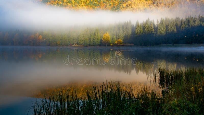 De herfstlandschap met kleurrijke zonsopgang bij St Ana Lake, Transsylvanië, Roemenië stock afbeeldingen