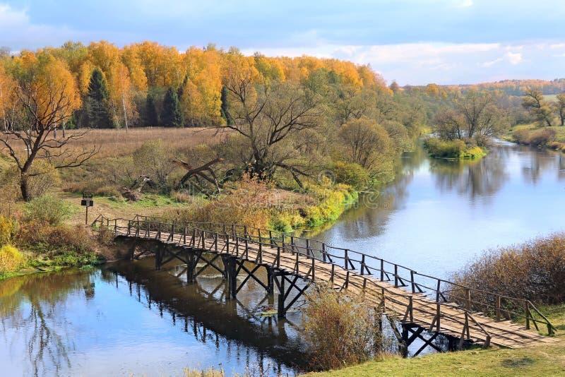 De herfstlandschap met rivier en houten brug royalty-vrije stock afbeelding