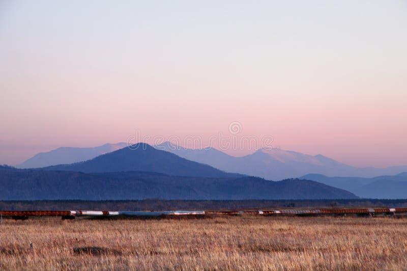 De herfstlandschap met sneeuwdiebergen achter gebied met droog geel gras tijdens spectaculaire kleurrijke zonsondergang wordt beh stock foto